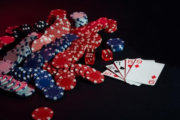 Casino-chips und karten auf schwarzer tischoberfläche. glücksspiel, glück, spiel und unterhaltungskonzept - nahaufnahme. online-poker. platz kopieren. ideal für werbung. stillleben