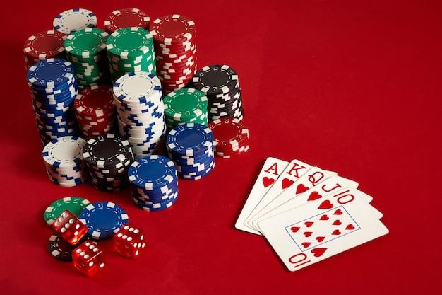 Casino-glücksspiel-poker-ausrüstung und unterhaltungskonzept - nahaufnahme von spielkarten und chips auf rotem hintergrund. royal flush herz. casino-hintergrund. platz kopieren. stillleben