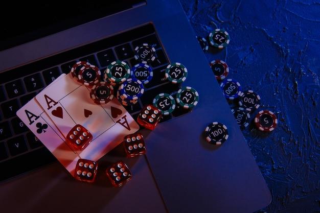 Casino spielen online-konzept. spielen von chips, karten und würfeln auf der tastatur des laptops