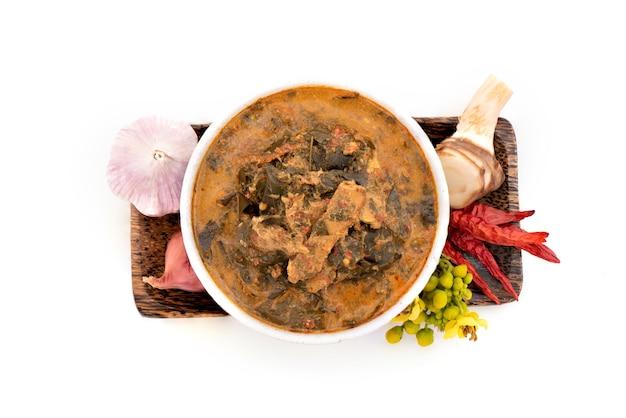 Cassia curry mit gegrilltem schweinefleisch und zutaten auf weißem hintergrund. ansicht von oben, flach.