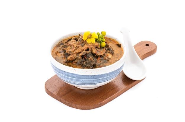 Cassia curry mit gegrilltem schweinefleisch und zutaten auf weißem hintergrund.