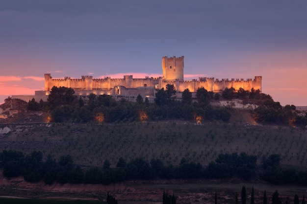 Castillo de peafiel in der provinz valladolid beleuchtet bei sonnenuntergang von weitem gesehen goldenes licht