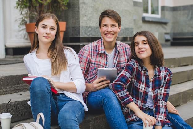 Casual content studenten posieren auf treppen
