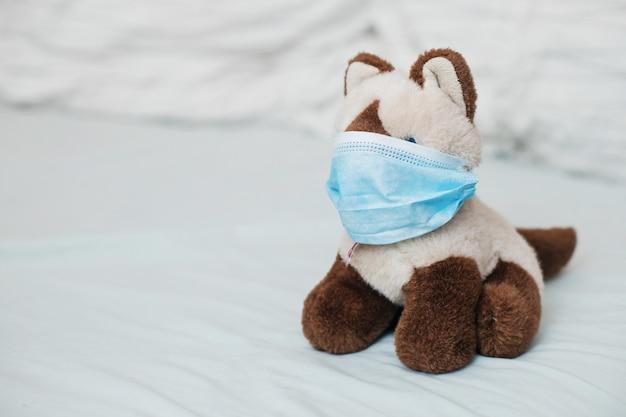 Cat siamese mit medizinischen masken auf dem bett. kranke krankheit bei kindern. coronovirus, quarantäne, epidemie, pandemie, erkältung, krankheit. medizinkonzept und gesundheit.