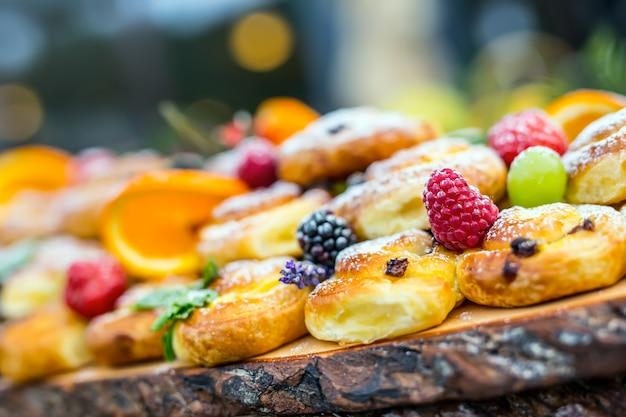 Catering-buffet-essen im freien. kuchen bunte frische früchte beeren orangen trauben und kräuterdekorationen.