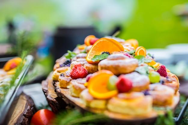 Catering buffet essen im freien kuchen bunte frische früchte beeren orangen und kräuterdekorationen