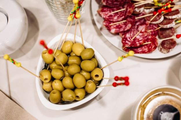 Catering, nahaufnahme von festlichen appetitlichen oliven, wurstscheiben, gesunde snacks auf dem banketttisch, partyessen. foto in hoher qualität