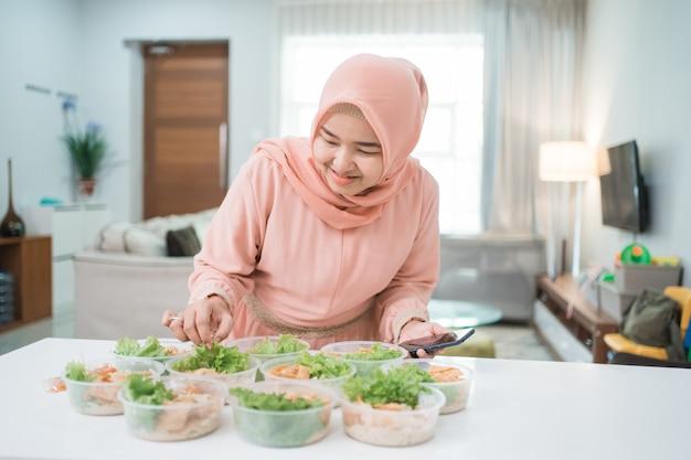Catering-service für muslimische asiatische frauen, der die brotdose für die online-bestellung zum mitnehmen vorbereitet