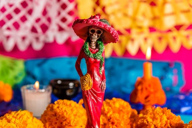 Catrina am altar, mit cempasuchil-blüten und gehackten papieren, tag der totenfeier