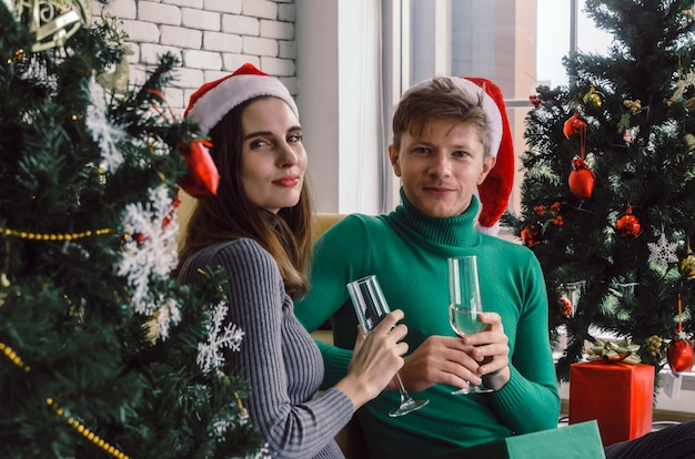 Caucasian süßes paar mit roten nikolausmütze genießen champagner trinken und blick in die kamera mit weihnachtsbaum im haus zu feiern