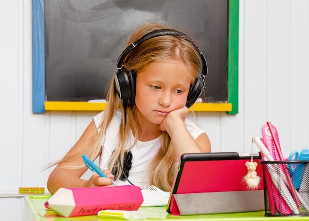 Causacian niedlichen schulkind mit kopfhörern ist auf langweilige online-heimunterricht.