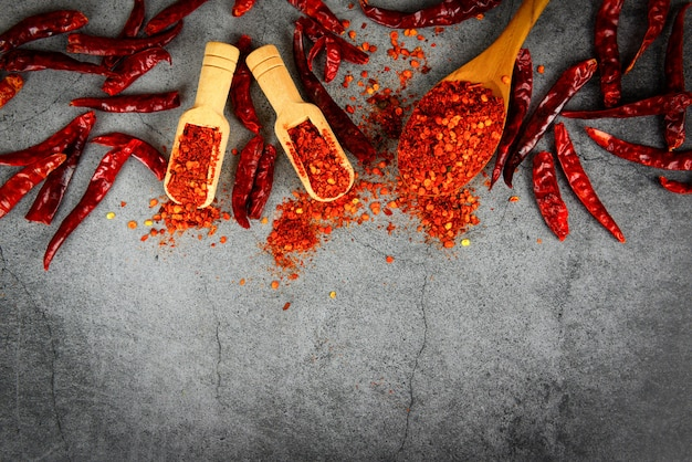 Cayenne-pfeffer auf gewürzen des hölzernen löffels und getrockneten paprikapfeffern, gruppe glühendes paprikapulver auf dem asiatischen lebensmittel der draufsichtbestandteil-tabelle des schwarzblechs würzig in thailand