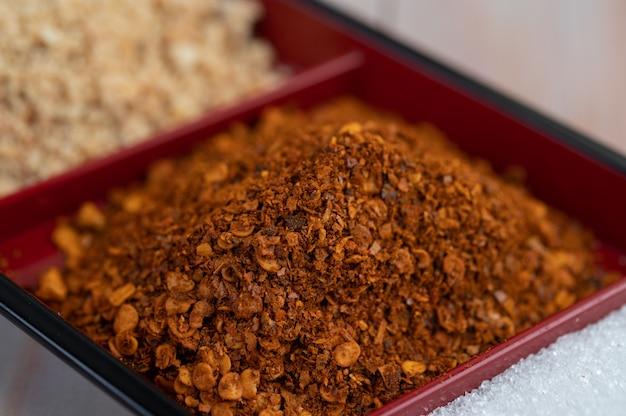 Cayenne-pfeffer in einer tasse auf dem holzboden.