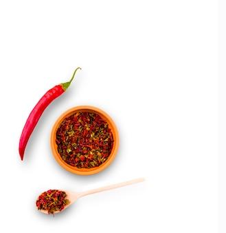 Cayenne-pfeffer und rote paprika auf teller und holzlöffel auf weißer wand.