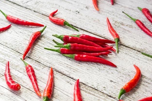 Cayennepfeffer des roten paprikas oder der paprikas auf weißem holztisch