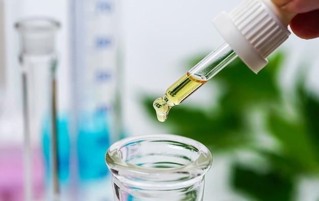 Cbd hanföl hand hält tröpfchen cannabisöl vor verschwommenem becherhintergrund