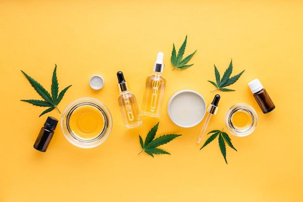 Cbd-öl, hanftinktur, cannabiskosmetikprodukt zur hautpflege mit cannabinoid. alternative medizin, pharmazeutisches medizinisches cannabis. sorten von ätherischem hanföl, serumbutter auf gelb.