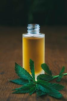 Cbd-ölspender neben cannabisblatt auf holzoberfläche mit dunklem hintergrund alternativmedizin