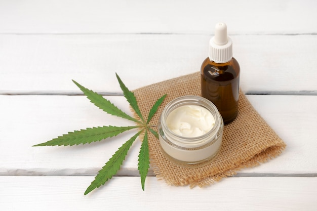 Cbdinfused gesichtscreme und serum mit cannabis grünem blatt auf weißem holzhintergrund mit kopierraum