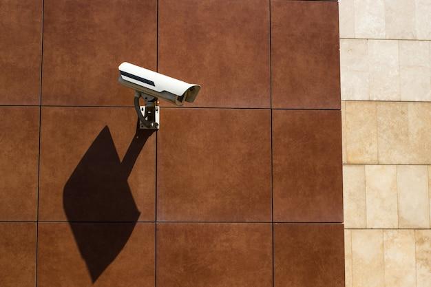 Cctv-kamera installiert in einer braunen fliesenwand eines einkaufszentrums zur überwachung der sicherheit auf einem parkplatz