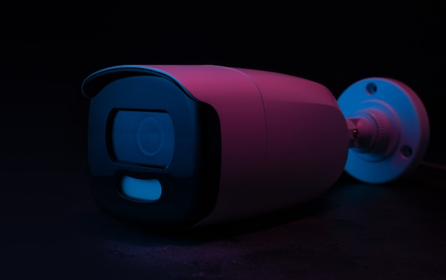 Cctv-kamera sicherheit in neonlicht auf dunkler oberfläche.