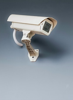Cctv-überwachungskamera an der wand auf grauem hintergrund