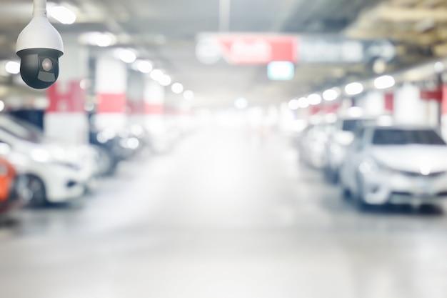 Cctv-überwachungskamera auf unschärfentiefgaragenparkplatz mit licht auf ausgangsweg