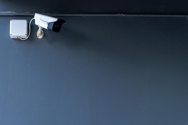 Cctv-überwachungskameraausrüstung wird entlang der wand eines dunklen modernen gebäudes installiert