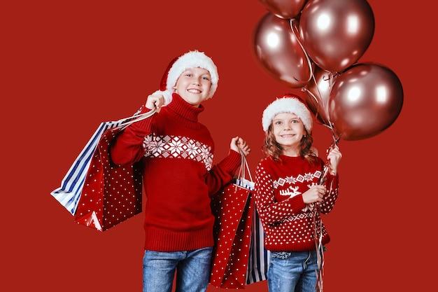 Ccute geschwister im roten pullover, der einkaufstaschen hält