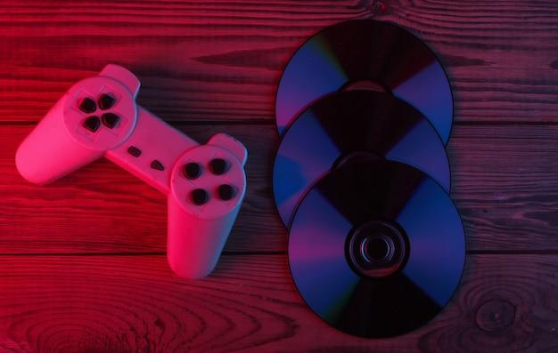 Cd-discs, gamepad auf holzoberfläche. neonrotes und blaues licht
