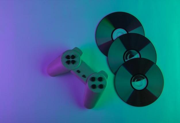 Cd-discs und gamepad mit neongrünem und lila licht