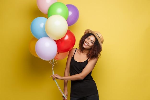 Celebration concept - close up portrait glücklich junge schöne afrikanische frau im schwarzen t-shirt lächelnd mit bunten party ballon. gelbe pastellstudio hintergrund.