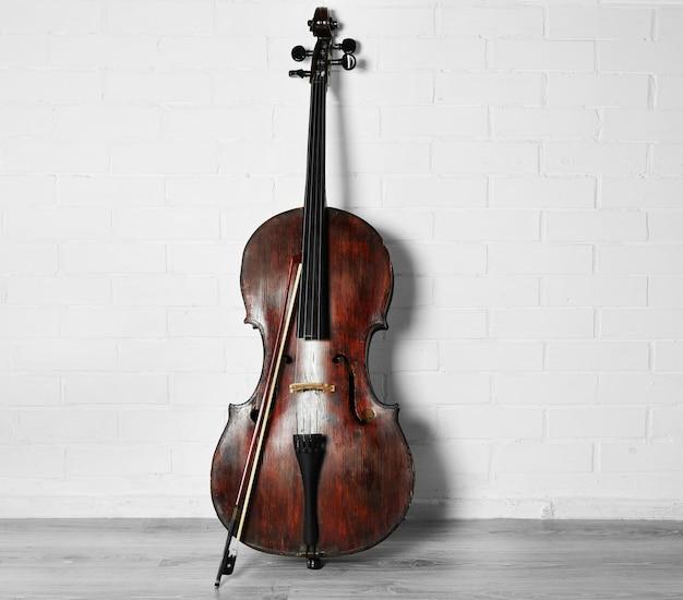 Cello auf weißer backsteinwandoberfläche