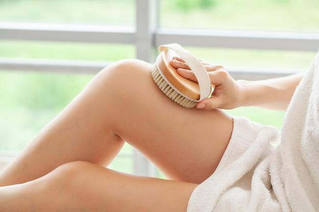 Cellulite-behandlung, frauenarm, der trockene bürste von ihrem bein hält.