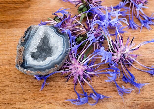 Centaurea montana und quarz vor holzbrett