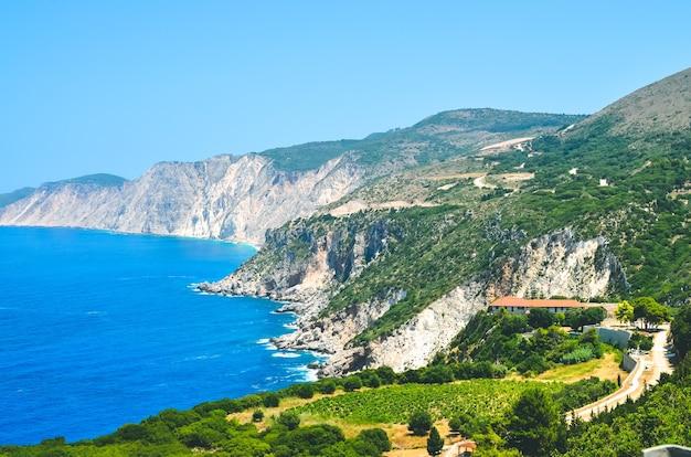 Cephalonia uferklippen und blaues küstenmeerwasser. olivenplantage im vordergrund