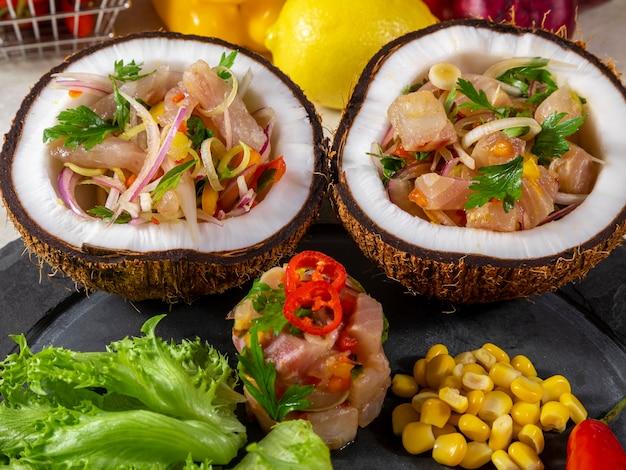 Ceviche-gericht - vorspeise aus frischem fisch, mariniert in zitrusfrüchten mit tropischen früchten, serviert in kokosnussschalen.