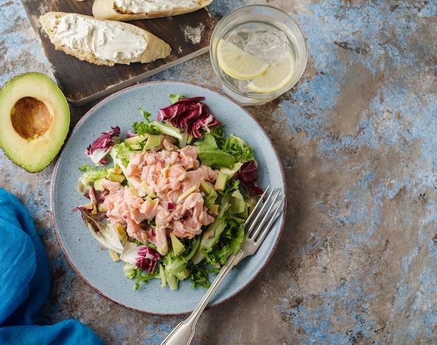 Ceviche ist ein traditionelles gericht aus peru. in zitrone marinierter lachs mit frischem salat, avocado und zwiebeln