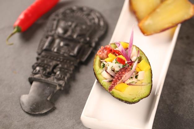 Ceviche mit avocado und wegerich. typisch peruanisches essen.
