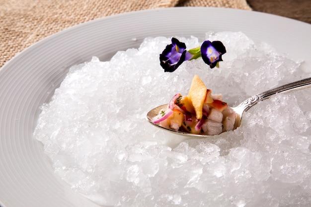 Ceviche serviert auf alten löffeln in der platte mit eis. lecker.