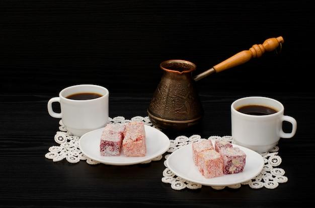 Cezve, bunte türkische freude und zwei tasse kaffees auf dem spitzeserviettenschwarzhintergrund