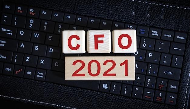 Cfo 2021 konzept. holzwürfel auf einer schwarzen tastatur