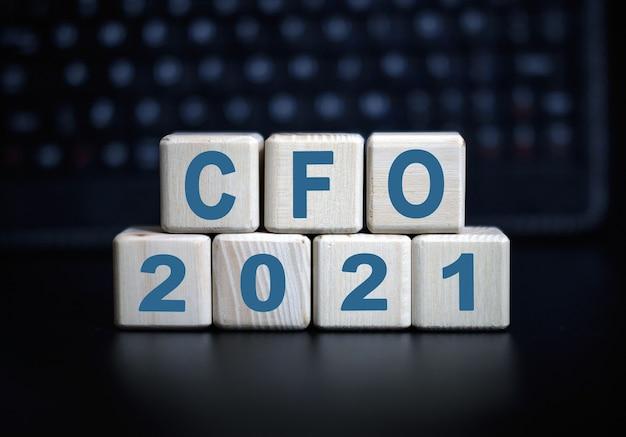 Cfo-text im konzept 2021. holzwürfel auf einer schwarzen tastatur