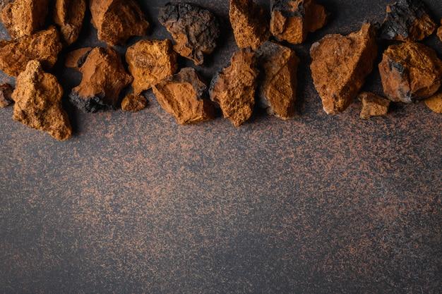 Chaga birke essbare pilze auf braun. trendy gesundes superfood für aufguss, tee.