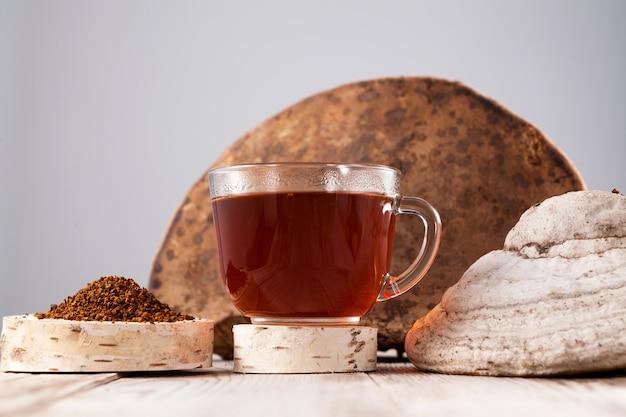 Chaga-tee - ein starkes antioxidans, stärkt das immunsystem, hat entgiftungsqualität und verbessert die verdauung. gesundes getränk in einer klaren tasse neben einem ganzen birkenpilz und gemahlenem pulver.