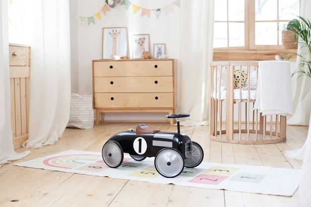 Chalet-baby-schlafzimmer-innenraum mit gemütlichem wiegen-bett. hellbrauner kindlicher raum mit hölzernem feldbett. gemütliches design im hygge-stil. öko-haus. retro kinder-rennwagen. rustikal. kindergarten. skandinavisch