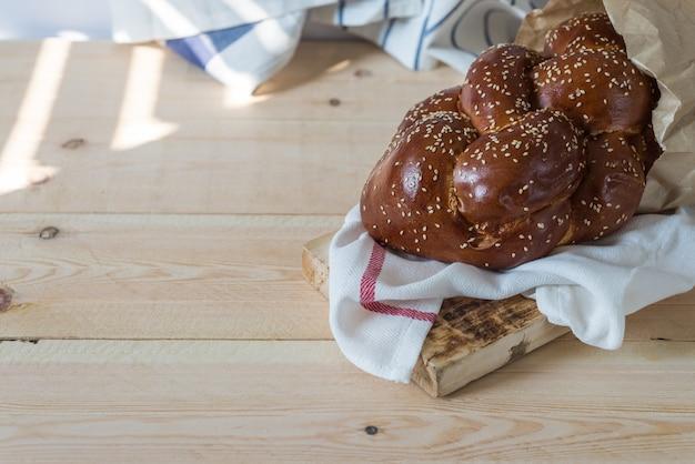Challah-brot oder traditionelles jüdisches brot auf einer hölzernen platte auf holztisch