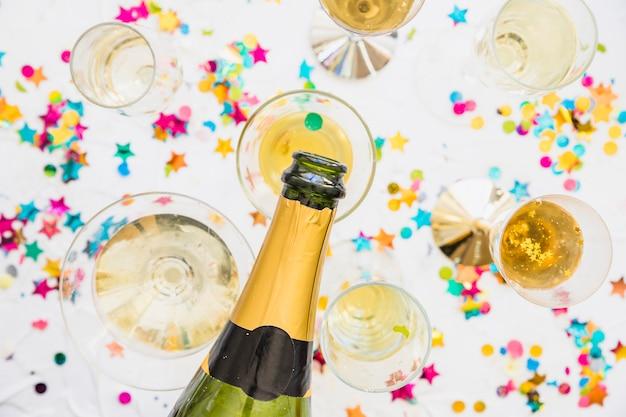 Champagne, die in glas auf tabelle gießt