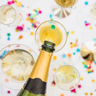 Champagne, die in glas auf weiße tabelle gießt