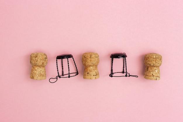 Champagne-korken und muselets auf rosa papierhintergrund mit kopienraum. close up gebrauchte holzstopfen. konzept für party oder urlaub.